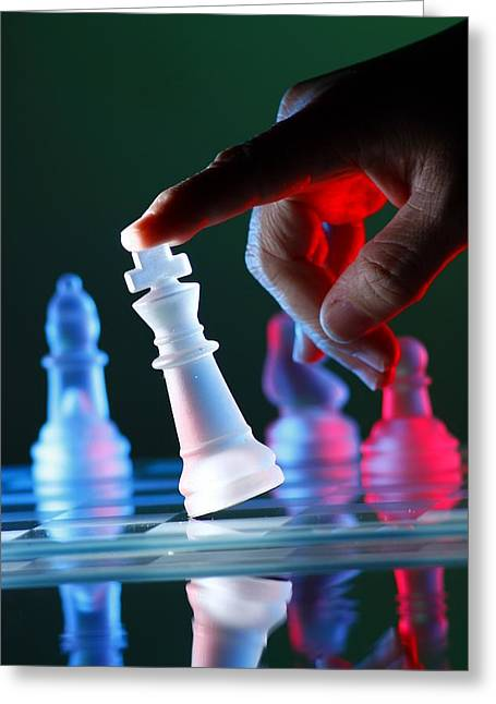 Glass Reflecting Greeting Cards - Finger tilting a chess piece on Chess Board Greeting Card by Jun Pinzon