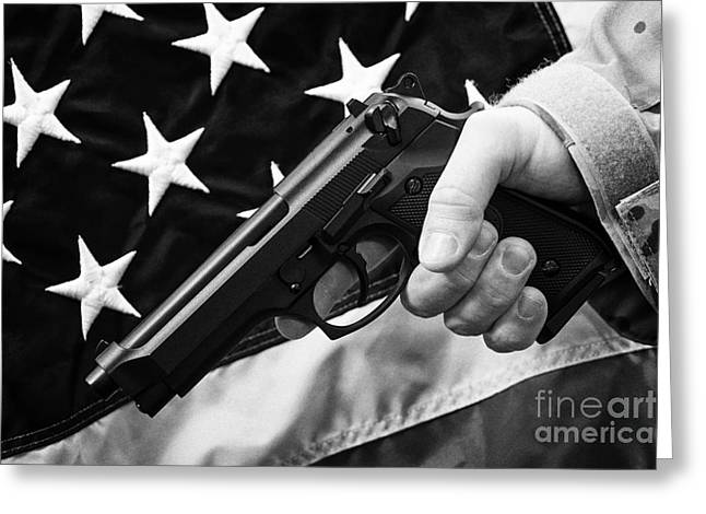 Holding Gun Greeting Cards - Man In Fatigues Holding Beretta Handgun In Front Of United States Of America Flag Greeting Card by Joe Fox