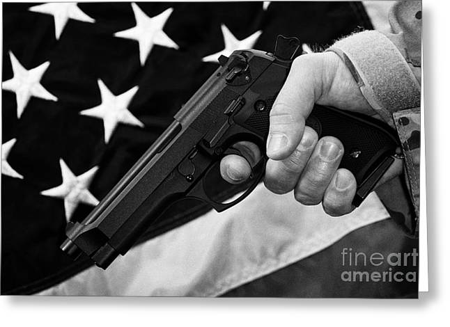 Holding Gun Greeting Cards - Man In Fatigues Holding Beretta Handgun With Finger On The Trigger In Front Of United States Of America Flag Greeting Card by Joe Fox