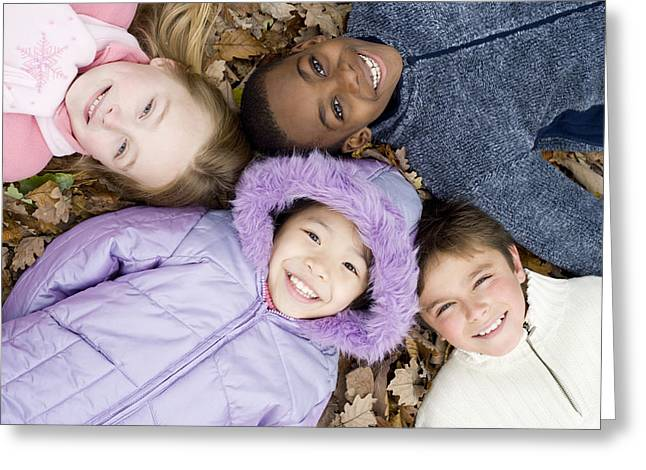 Nine Sisters Greeting Cards - Smiling Children Lying On Autumn Leaves Greeting Card by Ian Boddy