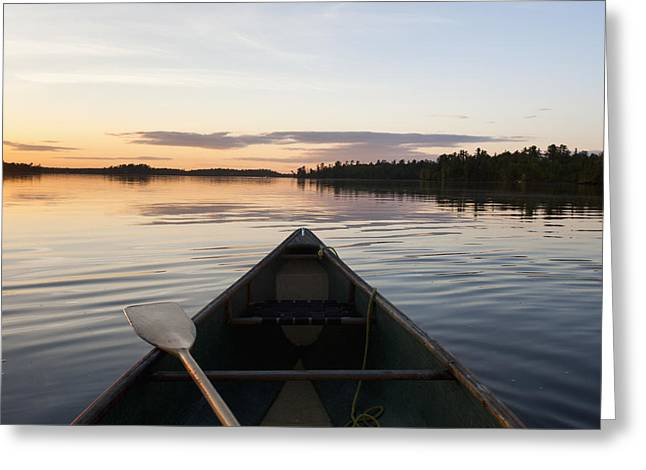 Reflections Of Sky In Water Greeting Cards - A Boat And Paddle On A Tranquil Lake Greeting Card by Keith Levit
