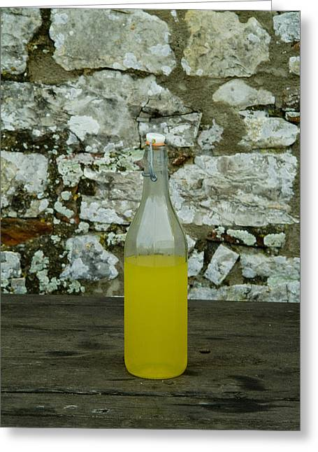 Chianti Greeting Cards - A Bottle Of Limoncello Sits On A Picnic Greeting Card by Todd Gipstein