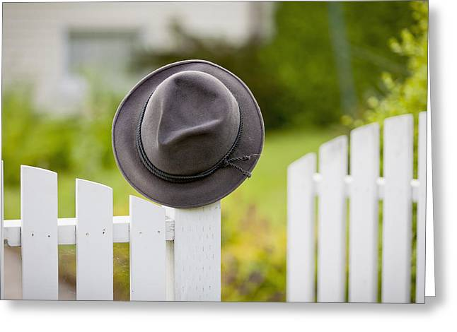 Differential Focus Greeting Cards - A Hat Hanging On The Post Of A White Greeting Card by Lorna Rande