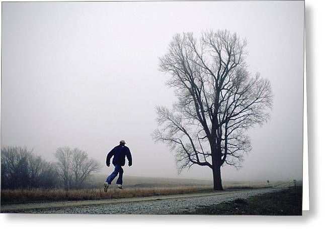 Gravel Road Greeting Cards - A Man Leaps In The Air On A Gravel Road Greeting Card by Joel Sartore