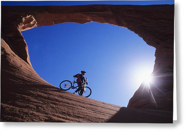 Quite Photographs Greeting Cards - A Mountain Biker Stands Under An Arch Greeting Card by Bill Hatcher