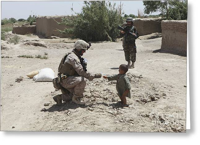 Civilians Greeting Cards - A U.s. Marine Gives Candy To An Afghan Greeting Card by Stocktrek Images
