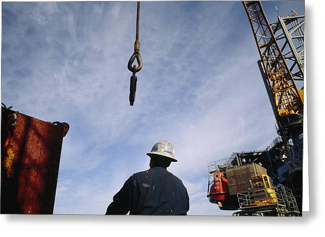 Oil Platform Greeting Cards - A Worker Uses A Crane And Hoist To Lift Greeting Card by Justin Guariglia