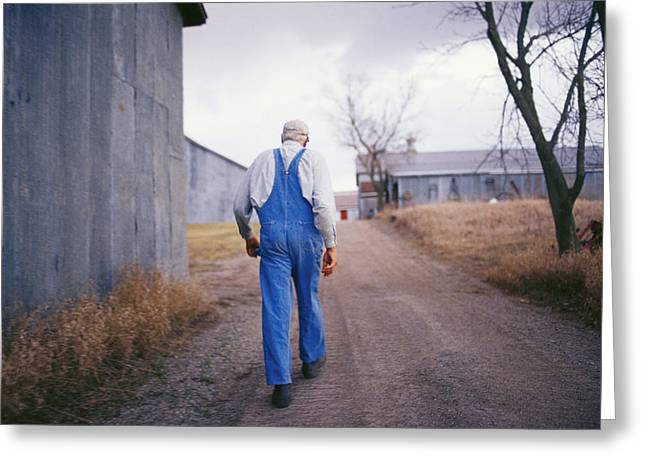 Farmers And Farming Greeting Cards - An Elderly Farmer In Overalls Walks Greeting Card by Joel Sartore