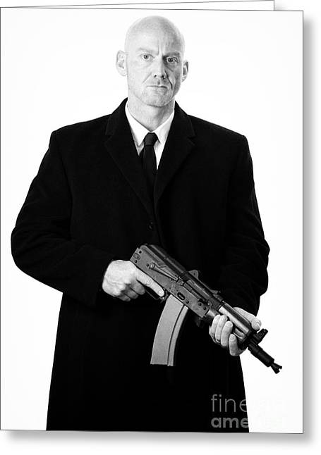 Ak47 Greeting Cards - Bald Headed Man Wearing Heavy Black Overcoat Holding Ak-47 Greeting Card by Joe Fox