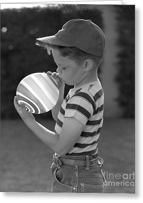 Boy Blowing Up A Striped Balloon Greeting Card by Pound/ClassicStock
