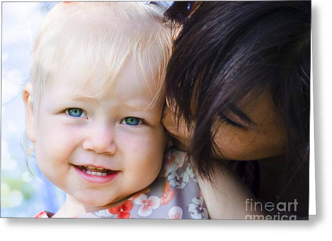 Caring Mother Greeting Cards - Brunette mother kissing blonde daughter at park Greeting Card by Ryan Jorgensen