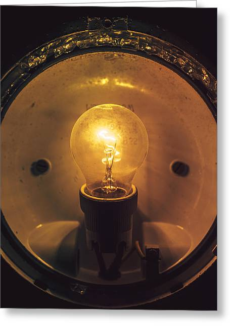 Edison Greeting Cards - Close up grungy glowing light bulb Greeting Card by Eduardo Huelin