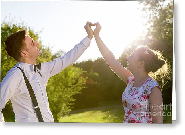 Dress Greeting Cards - Couple in love making a heart shape with their hands in sunshine Greeting Card by Michal Bednarek