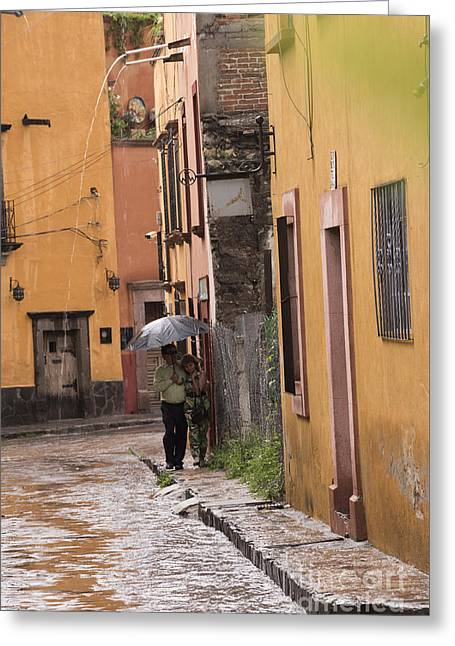 Puddle Greeting Cards - Couple walking in the rain through old San Miguel Mexico Greeting Card by Juli Scalzi