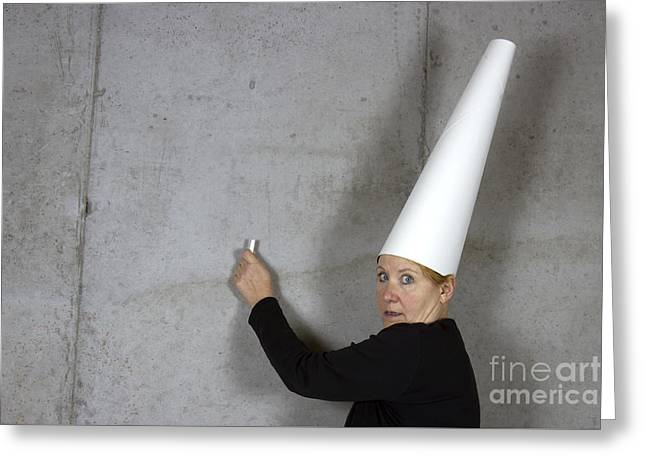 Dunce Greeting Cards - Dunce Cap on Woman Writing on Wall Greeting Card by Karen Foley