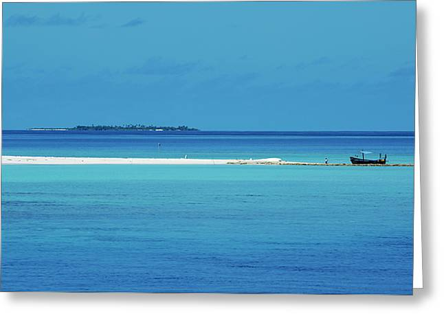 Fishing boat anchored on a white sand beach with a tropical island in the background in Maldives Greeting Card by Sami Sarkis