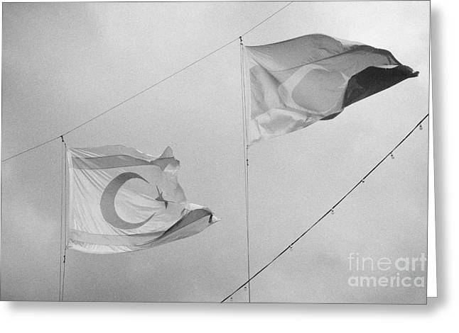 Flags Flying Greeting Cards - flags of turkey and TRNC turkish republic of northern cyprus flying in the sky above nicosia cyprus Greeting Card by Joe Fox
