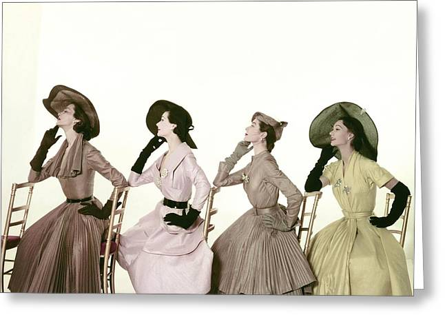 Ball Gown Greeting Cards - Four Models Sitting In A Line Facing Greeting Card by Conde Nast