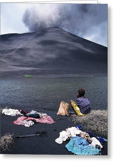 Washing Clothes Greeting Cards - Girl washing clothes in a lake with the Mount Yasur volcano emitting smoke in the background Greeting Card by Sami Sarkis
