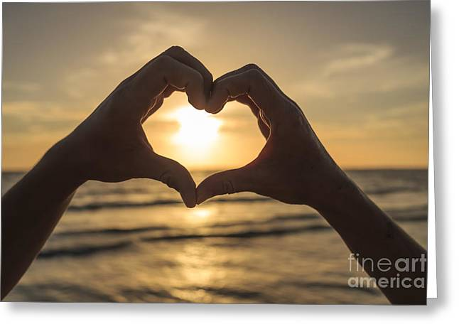 Hands Forming Heart Around Sunset Greeting Card by Edward Fielding