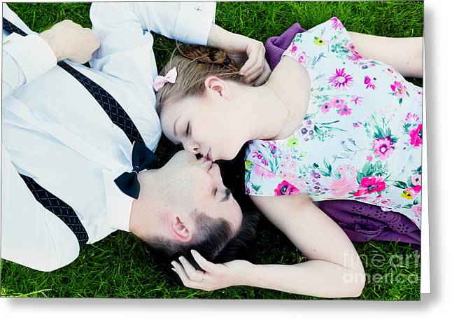 Suspenders Greeting Cards - Happy couple in love kissing while lying on summer grass Greeting Card by Michal Bednarek