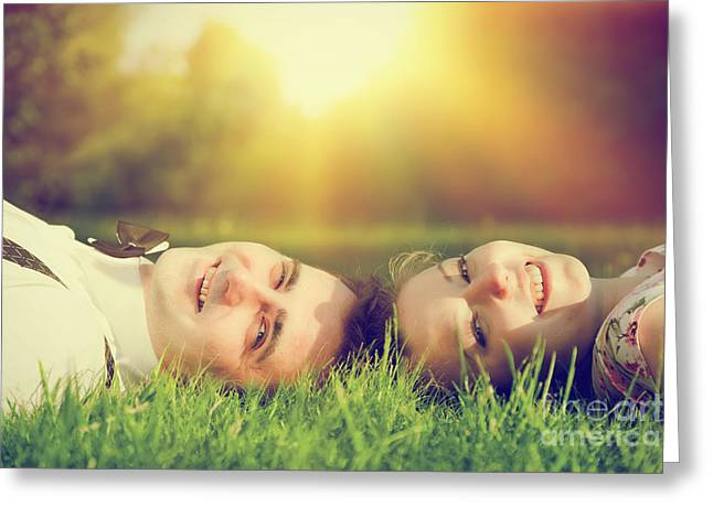 People Greeting Cards - Happy couple in love smiling while lying on summer grass Greeting Card by Michal Bednarek