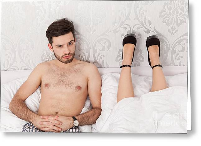 Man In Bed Wondering About The Lying Position Of His Girlfriend Greeting Card by Wolfgang Steiner