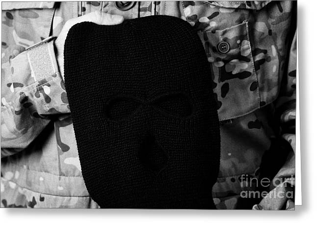 Balaclava Greeting Cards - Man In Combat Fatigues Holding Black Ski Mask Balaclava Greeting Card by Joe Fox