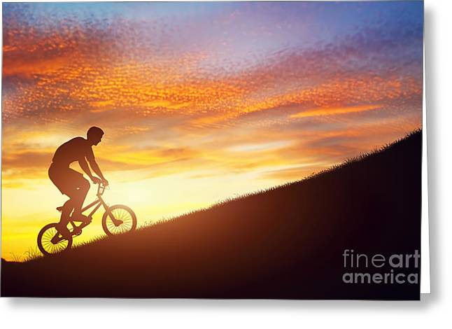 Ambition Greeting Cards - Man riding a bmx bike uphill against sunset sky Greeting Card by Michal Bednarek
