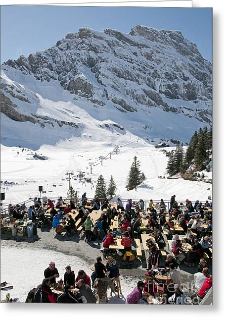 Landscape Photographs Greeting Cards - MOUNTAIN RESTAURANT IN ENGELBERG skiers in the spring sunshine at a cafe in swiss ski resort Greeting Card by Andy Smy