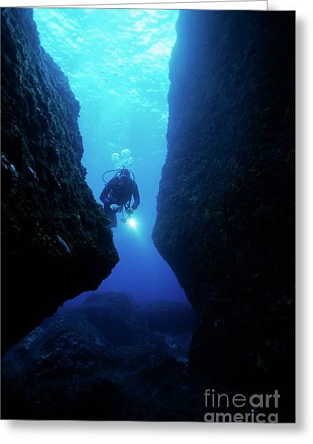 Undersea Photography Greeting Cards - One scuba diver shines an underwater light while swimming through a cave Greeting Card by Sami Sarkis