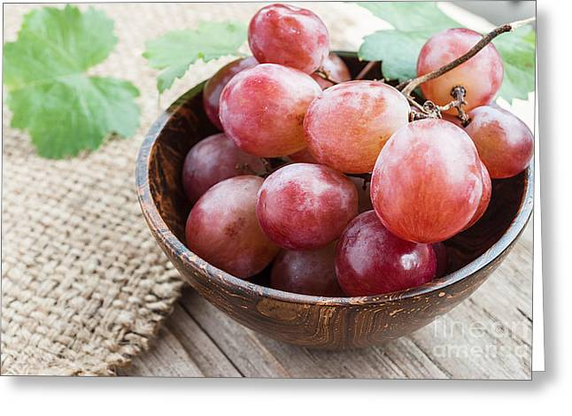 Grape Vineyard Greeting Cards - Red grape in wooden bowl on wooden table Greeting Card by Rakop Tanyakam