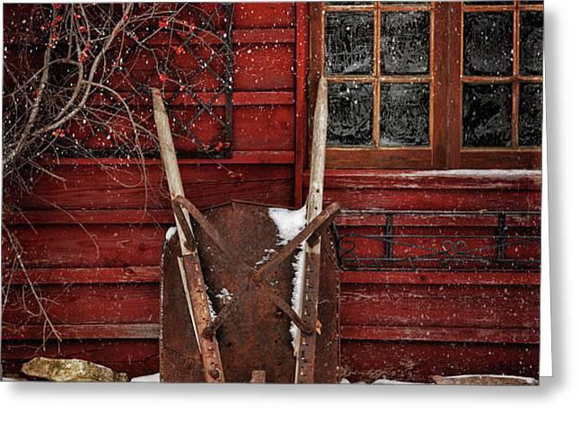 Rusty wheelbarrow leaning against barn in winter Greeting Card by Sandra Cunningham