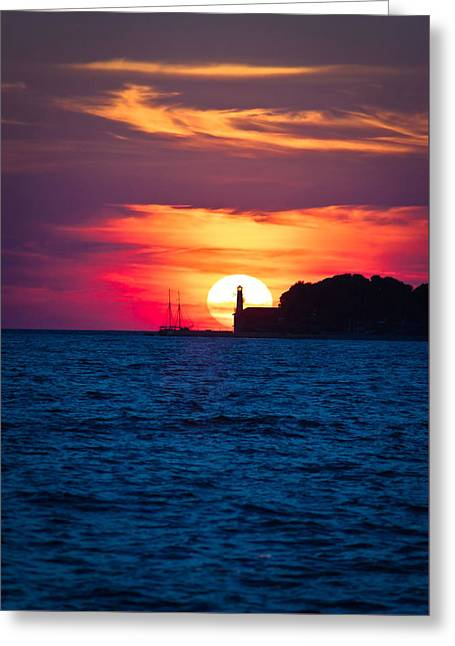Sailboat Ocean Greeting Cards - Sailboat and lighthouse on dramatic sunset Greeting Card by Dalibor Brlek