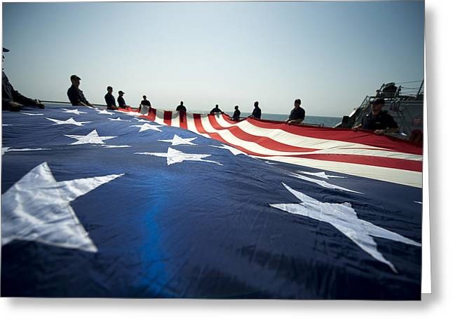Navy Greeting Cards - Sailors prepare a national ensign on the flight deck Greeting Card by Celestial Images