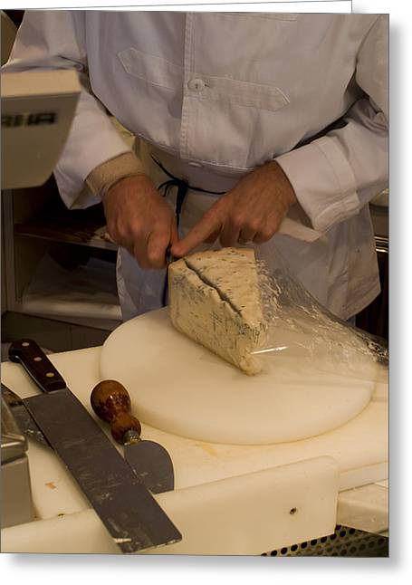Shop Keeper Cuts From A Wedge Of Cheese Greeting Card by Todd Gipstein