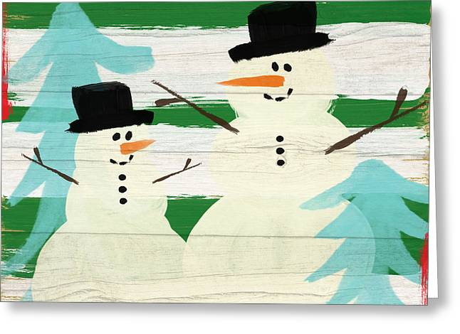 Snowmen With Blue Trees- Art By Linda Woods Greeting Card by Linda Woods