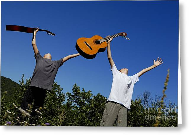 Serene People Greeting Cards - Two boys standing in meadow holding guitars in outstretched arms Greeting Card by Sami Sarkis