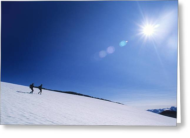 Burst Greeting Cards - Two Hikers Explore A Snowfield Greeting Card by Bill Hatcher