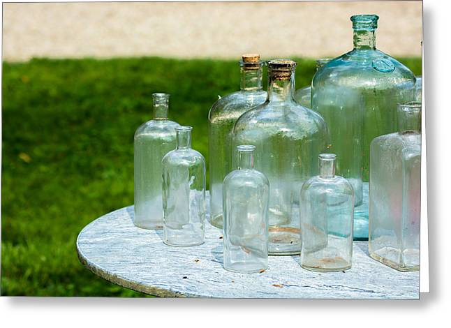 Glass Bottle Greeting Cards - Vintage Glass Bottles On Table Greeting Card by Andreas Berthold