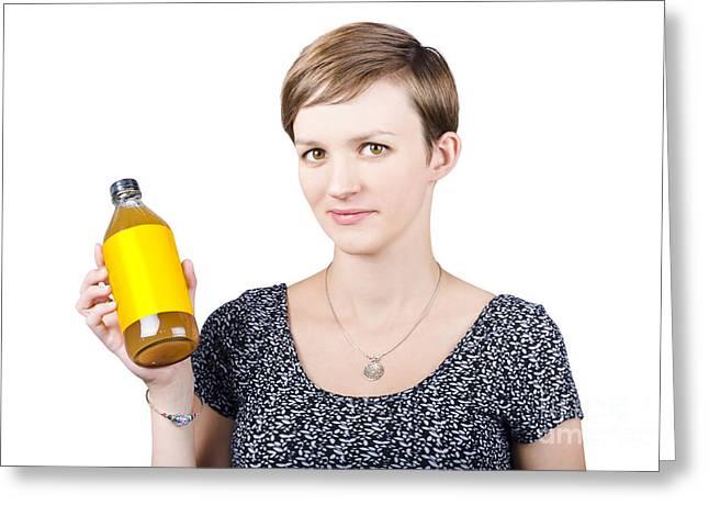 Vinegar Photographs Greeting Cards - Woman holding glass bottle of apple cider vinegar Greeting Card by Ryan Jorgensen