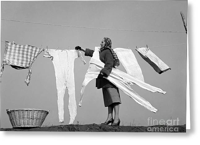 Woman Removing Frozen Clothes Greeting Card by Debrocke/ClassicStock
