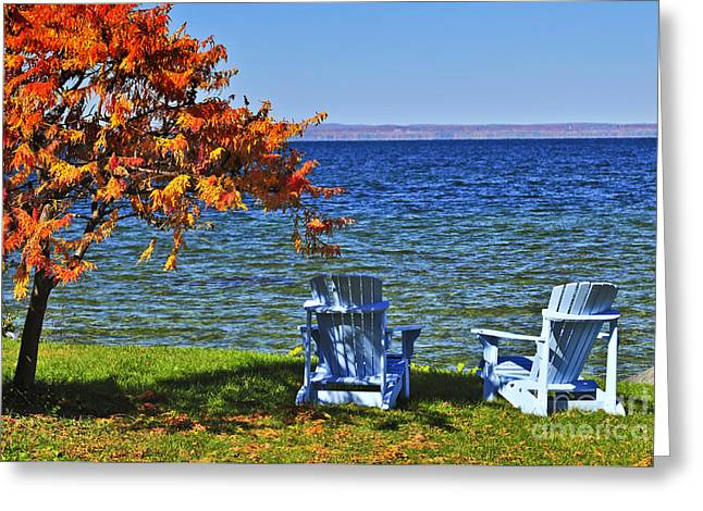 Lawn Greeting Cards - Wooden chairs on autumn lake Greeting Card by Elena Elisseeva