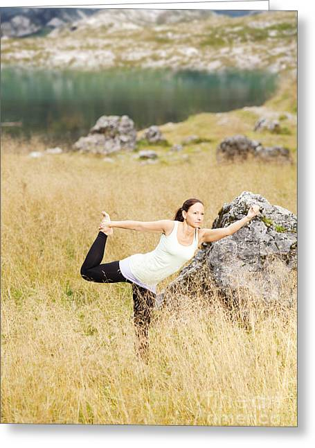 Yoga Greeting Cards - Yoga poses in high grass in front of a mountain lake in the Alps Greeting Card by Wolfgang Steiner