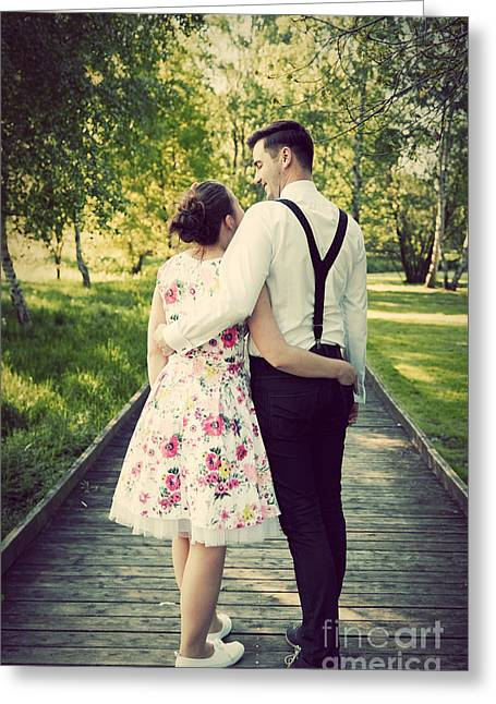 Suspenders Greeting Cards - Young couple embrace while standing on wooden path Greeting Card by Michal Bednarek