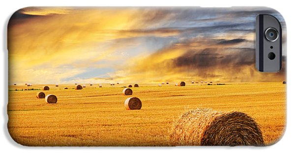 Scenery iPhone Cases - Golden sunset over farm field with hay bales iPhone Case by Elena Elisseeva
