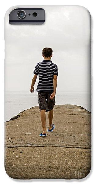 Moody Beach iPhone Cases - Boy walking on concrete beach pier iPhone Case by Edward Fielding