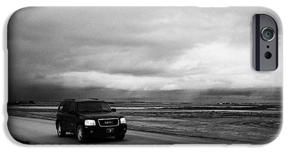 Winter Storm iPhone Cases - car driving on rural road as storm snow clouds forming over the prairies assiniboia Saskatchewan Can iPhone Case by Joe Fox
