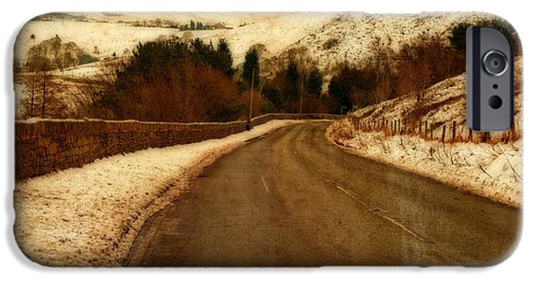Harsh Conditions iPhone Cases - Empty road through snow covered Yorkshire moors iPhone Case by Ken Biggs