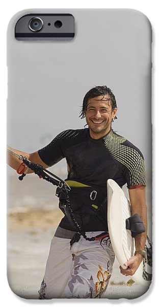 Kiteboarding iPhone Cases - Man Carrying Kitesurfing Board iPhone Case by Ben Welsh